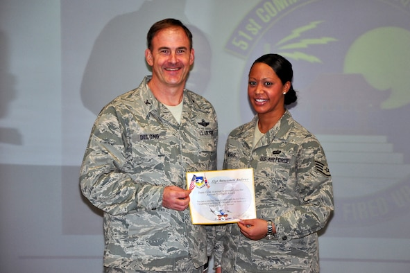 Col. Mark DeLong, 51st Fighter Wing Vice Commander, presents Staff Sgt. Antwaynete Andrews, 51st Communications Squadron, with a certificate for Airman Spotlight during a meeting Dec. 13, 2011. (U.S. Air Force photo/Tech. Sgt. Chad Thompson)