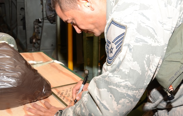 Over Fais Island, Micronesia - Master Sgt. John Hernandez, 44th Aerial Port Squadron Air Transportation, writes a get well message on a pallet filled with medical supplies that?s about to be dropped by parachute 300 feet to the island Fais to treat an outbreak of dengue fever.  The island of Fais is located within the Yap state of the Micronesian Islands, and is one of the more than 50 islands that will receive care packages this holiday season as part of Operation Christmas Drop.  (U.S. Air Force photo/Senior Airman Veronica McMahon)