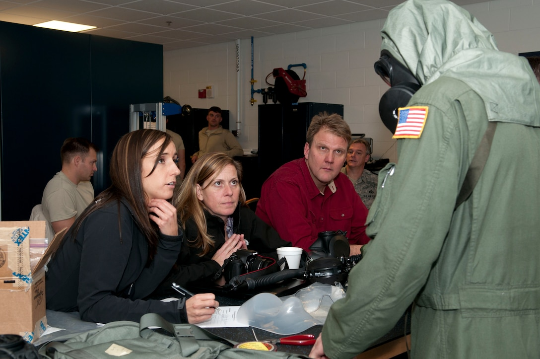 Erin Kennedy, Nicole Fletcher, and Wayne Shira, Joint Service Aircrew Mask - Fixed Wing (JSAM-FW) research team members, listen to feedback from Staff Sgt. Alex Whalton, 167th Airlift Squadron flight engineer, as he wears the M-53 mask and hood, part of the JSAM-FW system. A Department of Defense research team working on the development of aJSAM conducted field assessments at the 167th Airlift Wing, West Virginia Air National Guard unit in Martinsburg, WV,  December 7, 2011. The team had aircrew in each of the flying positions don the mask and accompanying gear and perform their duties on a C-5 aircraft. (Air National Guard photo by Master Sgt. Emily Beightol-Deyerle)