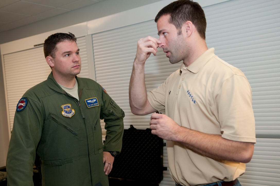 Steve Leadore, an equipment technician for the joint service aircrew mask - fixed wing (JSAM-FW) research team, explains the nosepiece for a mask to Technical Sgt. Michael Lindamood, a loadmaster for the 167th Airlift Squadron. A Department of Defense research team working on the development of a joint service aircrew mask conducted field assessments at the 167th Airlift Wing, West Virginia Air National Guard unit in Martinsburg, WV,  December 7, 2011. The team had aircrew in each of the flying positions don the mask and accompanying gear and perform their duties on a C-5 aircraft. (Air National Guard photo by Master Sgt. Emily Beightol-Deyerle)