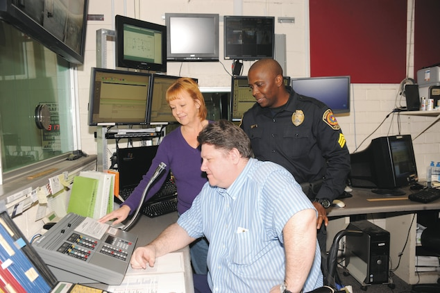 Robbin Lamb, spectrum and land mobile radio manager with Marine Corps Logistics Base Albany, demonstrates how to use the new radio dispatch console to Kevin Armstrong, sitting, emergency services   dispatcher, and Sgt. Charles Duncan, patrol sergeant/desk sergeant, Marine Corps Police Department, recently.