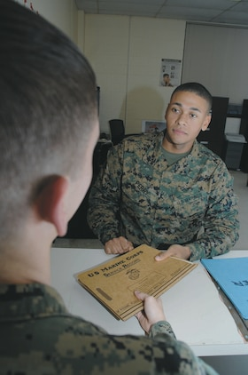Lance Cpl. Cameron Perry, administrative specialist with Marine Corps Logistics Base Albany, receives a service record book from a Marine at the counter inside Military Personnel Center, recently.