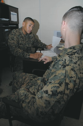 Lance Cpl. Cameron Perry, administrative specialist with Marine Corps Logistics Base Albany, combs through a Marine's service record book updating his personal information, inside Military Personnel Center, recently.