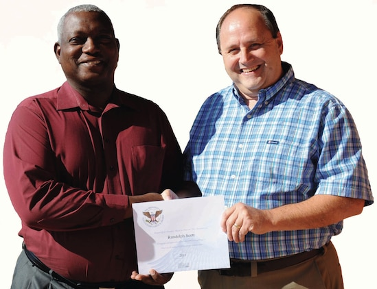 Michael Carroll, right, systems analyst, Marine Corps Systems Command, congratulates Randy Scott, project manager, MCSC, on his third consecutive President's Volunteer Service Award, recently. Scott has volunteered with the Albany Young Marines Program for eight years.