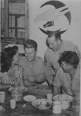 Members of the 35th PRS entertain Jinx Falkenburg.  From left to right are Jinx, Lt. Morris, First Sergeant Flavin and Sgt Shaylor.  First Sergeant John Flavin and Sgt Jack Shaylor were original members of the Oregon National Guard's 123rd Observation Squadron.  Note the early Redhawk emblem of the squadron on the wall behind, with twin tails evocative of the twin-boomed F-5 recon aircraft the squadron flew in the CBI.  The Redhawk is still used by the ORANG's 123rd Fighter Squadron today.