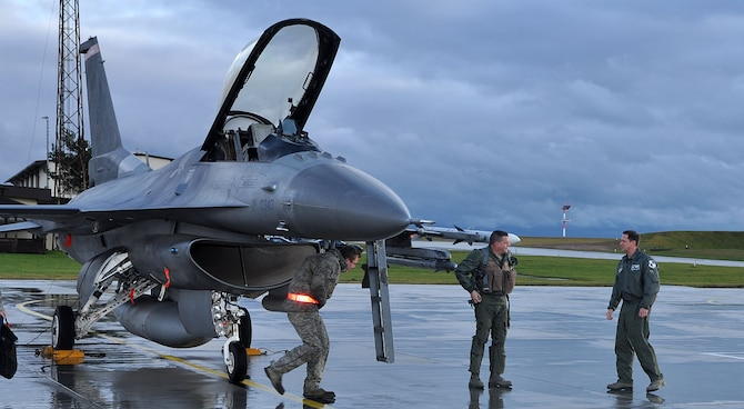 SPANGDAHLEM AIR BASE, Germany -- Lt. Col. Brian Egger, center, 480th Fighter Squadron F-16 Fighting Falcon pilot, is greeted by Col. David Lyons, 52nd Operations Group commander, after landing here Dec. 14. Egger reached his 4,000th total flying hour on this flight and is the 34th F-16 pilot in U.S. Air Force history to reach this milestone. Egger is stationed at Ramstein Air Base, but does flight qualifications and is an instructor pilot with the 480th FS here. (U.S. Air Force photo/Senior Airman Natasha Stannard)