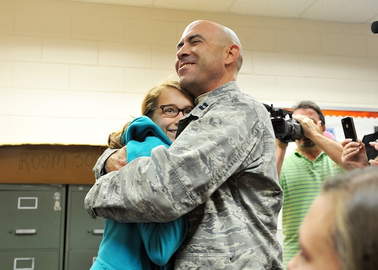 Capt. Nathan List hugs his 12-year-old daughter Chloe Dec. 9. Capt. List returned home early from Iraq to surprise his son James, 9, at Shirley Hills Elementary School, and Chloe at Warner Robins Middle School. List, who has been deployed since before July 4, was not expected home until after Christmas.  With President Obama's acceleration of the drawdown of troops, the Air Force Reserve Command captain made it home three weeks earlier than originally planned.  He and his wife, Lisa, first surprised Chloe at Warner Robins Middle, then went to Shirley Hills Elementary to surprise James. U.S. Air Force photo by Tommie Horton