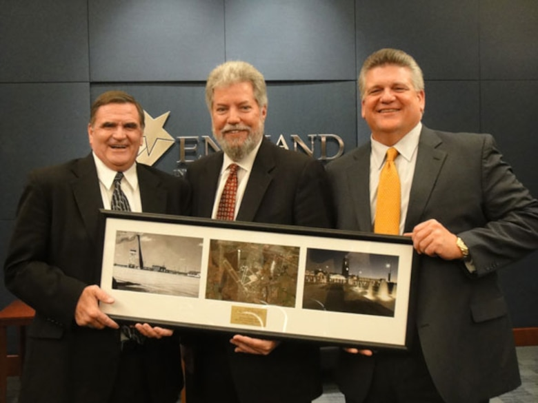 Air Force Real Property Agency Director Robert Moore presents a commemorative photo to Lance Harris, Chairman of the England Authority and Jon Grafton, Executive Director of the England Authority during the Whole Base Transfer Ceremony on December 8, 2011.