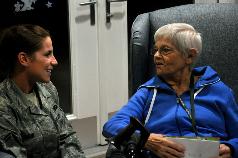 Airman 1st Class Stefanie Simon, 1st Special Operations Contracting Squadron, left, visits with Ruth Hunter, a resident of the Air Force Enlisted Village's Hawthorne House, at the house in Shalimar, Fla., Dec. 13, 2011. Simon and other Hurlburt Field Airmen delivered holiday cards to the widows of the Hawthorne House to spread holiday cheer. (U.S. Air Force photo/Staff Sgt. William Banton)(Released)