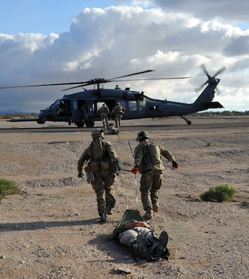 Pararescuemen drag patients on a sled to a HH-60G Pave Hawk helicopter during a mass causality drill as part of Operation Shocker, a training exercise designed to hone 943rd Rescue Group Airmen's combat-search-and-rescue skills. (U.S. Air Force Photo/ Master Sgt. Luke Johnson)
