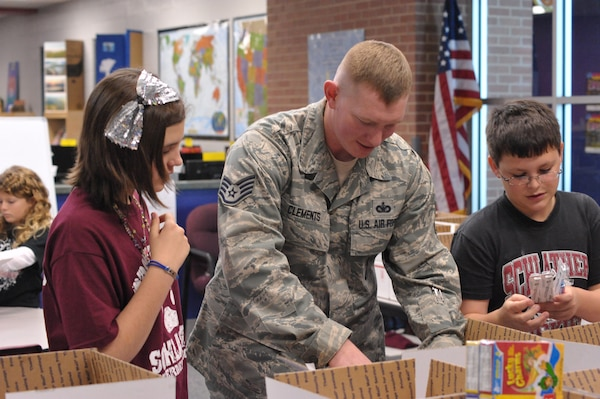 Staff Sgt. Joshua Clements, 902nd Security Forces Squadron, and Schlather Intermediate School sixth-graders, (from left) Isabelle Aimone, Mykiah Ausby and Nick Fulbright participate in Operation Shoebox Dec. 9 by preparing holiday care packages to be mailed to deployed Joint Base San Antonio service members.  (U.S. Air Force photo by Airman 1st Class Alexis Siekert)