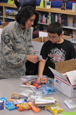 Master Sgt Karla Iglesias, Airman and Family Readiness Center NCO in charge, works with Matthew Avila, Schlather Intermediate School fifth-grader, to put together care packages for 35  deployed Joint Base San Antonio servicemembers. Through Operation Shoebox, the students were able to send packages spreading holiday cheer to deployed troops