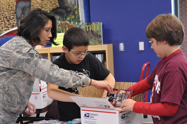 Master Sgt Karla Iglesias, Airman and Family Readiness Center NCO in charge, works with Matthew Avila, Schlather Intermediate School fifth-grader, to put together care packages for 35  deployed Joint Base San Antonio servicemembers. Through Operation Shoebox, the students were able to send packages spreading holiday cheer to deployed troops (U.S. Air Force photo by Airman 1st Class Alexis Siekert)
