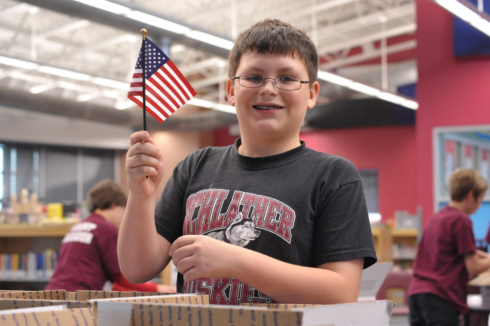 Carter Arispe, Schlather Intermediate School sixth-grader, waves an American flag while participating in Operation Shoebox Dec 9. The students sent care package to deployed Joint Base San Antonio servicemembers over the holidays. (U.S. Air Force photo by Airman 1st Class Alexis Siekert)