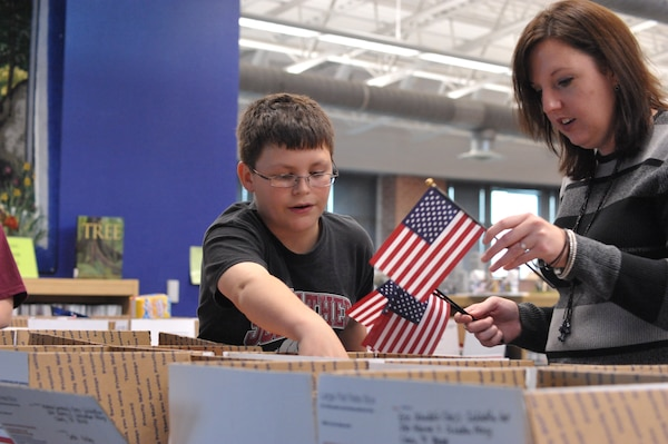 Carter Arispe, Schlather Intermediate School sixth-grader, and Carla Barnes, Schlather counselor, participate in Operation Shoebox Dec 9 by placing American flags into each care package to be sent to deployed Joint Base San Antonio servicemembers over the holidays.