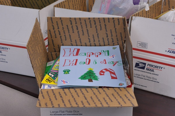 A handmade holiday card sits on top of a care package put together by Schlather Intermediate School's fifth and sixth grade students during Operation Shoebox Dec 9.(U.S. Air Force photo by Airman 1st Class Alexis Siekert)