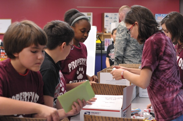 """Sixth-graders from Schlater Intermediate School participate in Operation Shoebox Dec. 9. Operation Shoebox shipped """"shoeboxes"""" to 35 deployed members. (U.S. Air Force photo by Airman 1st Class Alexis Siekert)"""