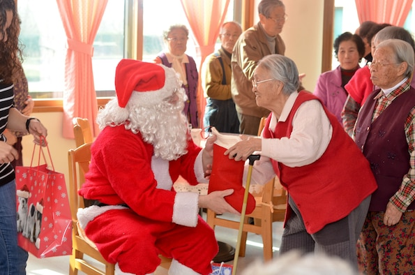 A member of the Wolf Pack dressed as Santa Claus, gives a stocking to a resident of the Heart of Jesus Senior Care elderly home during his visit there for a Christmas celebration in Gunsan City, Republic of Korea, Dec. 10, 2011. The senior center was host to many smiles, cake, joint decorating and singing classic Christmas carols. (U.S. Air Force photo by Senior Airman Derrick Schwieters/Released)