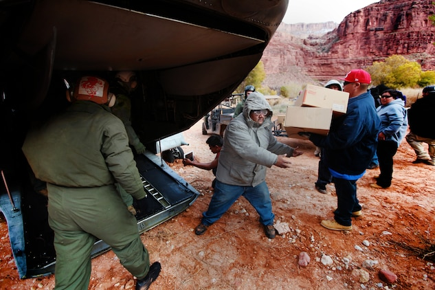 Marines from the U.S. Marine Corps Medium Helicopter Squadron 764 (the Moonlighters), 4th Marine Aircraft Wing, and Havasupai  tribal members offload a CH-46E helicopter Dec.14. he Moonlighters flew into Supai Village, Ariz., carrying toys, supplies and Santa Claus. The five airdrops completed by the Moonlighters were part of the Operation Havasupai, a collaboration of the Marine Corps Reserve and Toys for Tots program to help out people of the isolated Native American village located within the Grand Canyon. (U.S. Marine Corps photo by Lance Cpl. Marcin Platek)