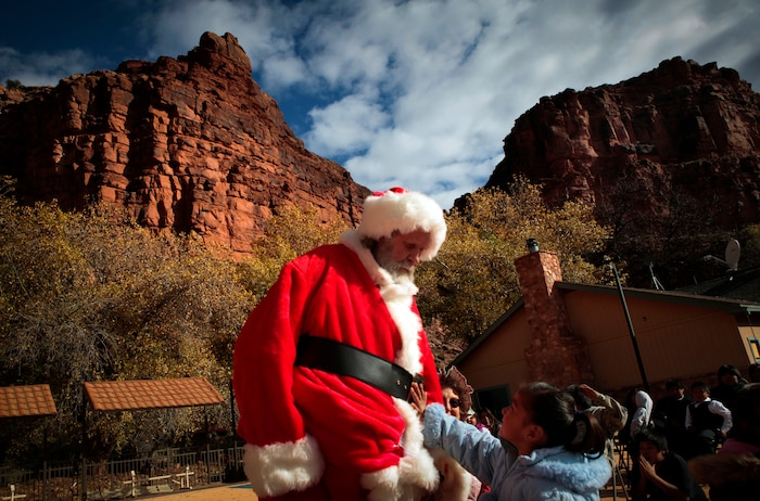 A young boy of the Havasupai tribe wrestles with his father for a gift bag flown into the Grand Canyon by U.S. Marine Corps Medium Helicopter Squadron 764 (HMM-764), 4th Marine Aircraft Wing. HMM-764's mission was to join the Flagstaff Community Toys For Tots Organization in delivering Santa Claus and toys to the children of the tribe, as well as conduct training exercises throughout the Grand Canyon as part of Operation Havasupai.