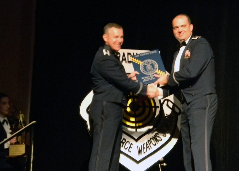 """B-2 bomber pilot Maj Ryan """"Poacher"""" Bailey, 131st Bomb Wing, Missouri Air National Guard, receives his  U.S. Air Force Weapons School graduation plaque on stage at the Flamingo Hotel and Casino, Dec 10.   He received the additional honor of being awarded Outstanding Graduate of his class.  (Air National Guard Courtesy Photo)"""