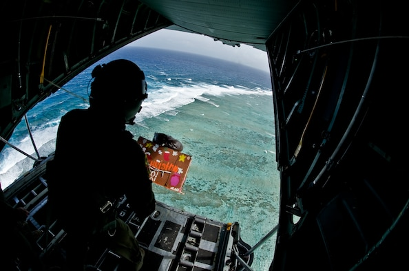 Staff Sgt. Kyle Favorite, 374th Airlift Wing loadmaster, from Yokota Air Base Japan , pushes a pallet out of a C-130 Hercules over the island of Fais, Dec. 15. Operation Christmas Drop 2011 is an annual event, airlifting pallets for 57 islands of Micronesia. The pallets contain school supplies, toys, medical supplies, and common day items. (U.S. Air Force photo/Staff Sgt. Alexandre Montes)