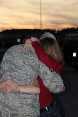 Tech. Sgt. Shawn Gambill, a 53rd Combat Communications Squadron cyber systems operations technician, embraces his wife, Misty, at a welcome home ceremony Dec. 19.  The returning communicators closed Sather Air Base operations and were some of the last Airmen to leave Iraq. U.S. Air Force photo by Robert Talenti