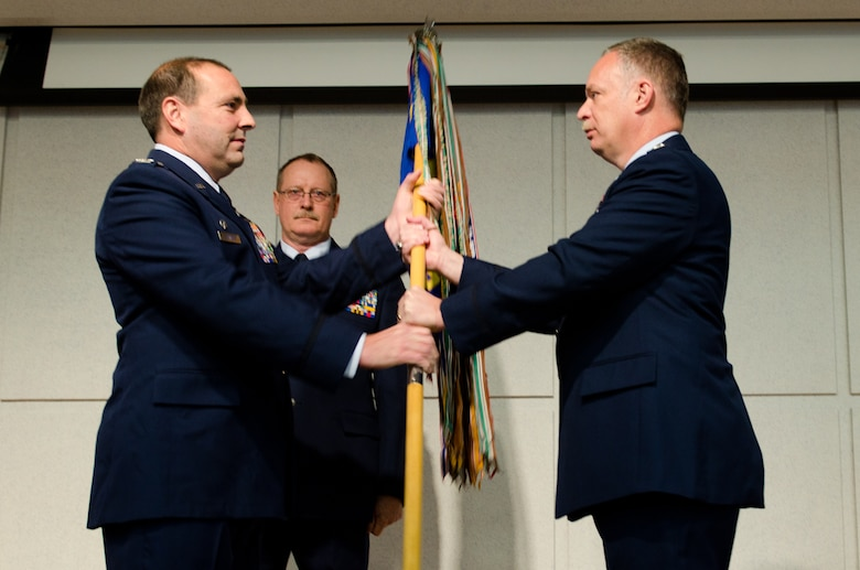 Col. Ralph Schwader, 139th Airlift Wing vice commander, hands the 139th Operations Group flag to Lt. Col. Dave Halter, 139th OG commander, during a change of command ceremony Dec. 4, 2011 at Rosecrans Air National Guard Base, St. Joseph, Mo. (Missouri Air National Guard photo by Senior Airman Kelsey Stuart)