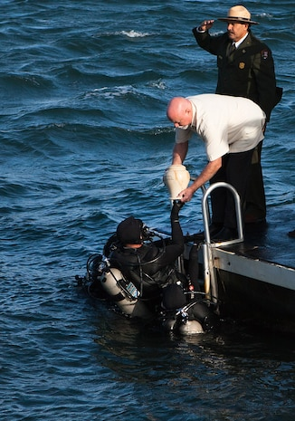 Jerry Cabiness, son of Frank R. Cabiness, passes the urn containing his father's remains to the National Park Service Dive Team during his interment ceremony here Dec. 23. Survivors of the attacks of the USS Arizona can be interred at the USS Arizona Memorial.