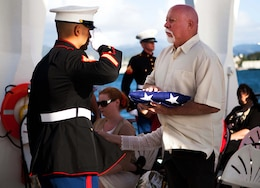 Staff Sgt. Raymond M. Shinohara, Marine coordinator for the interment ceremony, salutes Frank R. Cabiness' flag after presenting it to his son, Jerry Cabiness, at the USS Arizona Memorial here Dec. 23. Although Frank Cabiness passed away in 2002, he was granted his final wish and rejoined his fallen comrades after being laid to rest inside the hull of the USS Arizona.