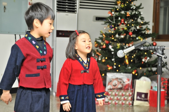 Children from the Samsung Orphanage in Gunsan City, Republic of Korea, perform for the Airmen of the 8th Security Forces Squadron Dec. 22, 2011. Airmen provided each child with three Christmas gifts. The defenders also served dinner and delivered a little Christmas cheer. (U.S. Air Force photo by Senior Airman Brittany Y. Auld/Released)
