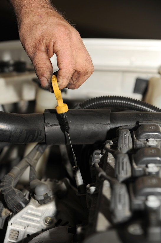 Jerry Cazeault uses a dipstick to check the oil after a brake change on Seymour Johnson Air Force Base, N.C., Dec. 27, 2011. The reading from the dipstick allows a mechanic to know if the oil in a car is too low, which could cause damage to an engine. Cazeault is a 4th Force Support Squadron auto skills development mechanic from Woonsocket, R.I. (U.S. Air Force photo by Senior Airman Whitney Stanfield)