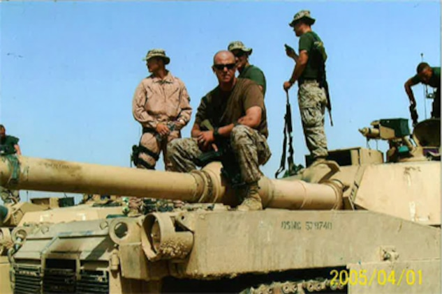 Sgt. Josh Cooley takes a break from his work on top of an M1 A1 Abrams tank in Iraq July 1, 2005, just days before his convoy was blown up by an improvised explosive device. Cooley, a crew chief for amphibious assault vehicles, lost a third of his brain in the blast and sustained significant burns over much of his body. Over the next six years, Cooley defied all odds by steadily improving until he was able to walk, stand, talk and perform daily tasks.