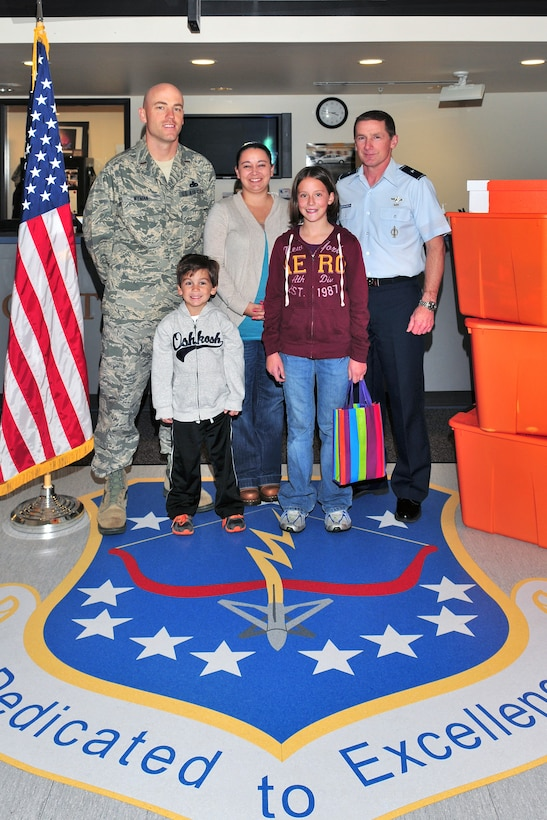 115th Fighter Wing Maintenance Operations Flight Supervisor 2nd Lt. Brian Wyman, his wife Shawna, lead volunteer for the unit's Airman and Family Readiness Program, and son Paxton, join 115th Fighter Wing Commander, Brig. Gen. Joseph Brandemuehl in recognizing the selfless efforts of their daughter Niki on November 02, 2011. Niki celebrated her 12th birthday by requesting donations for deployed unit members in lieu of gifts, which helped make possible the shipment of dozens of care packages to Wisconsin National Guard members spending their holidays far from home and family.