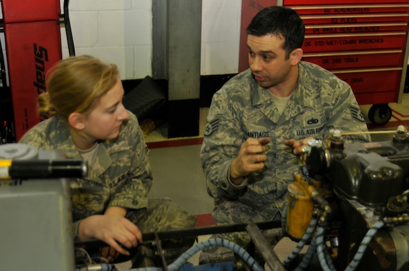 ROYAL AIR FORCE LAKENHEATH, England ? Staff Sgt. Nathan Santiago, 372nd Training Squadron, Detachment 16 Aerospace Ground Equipment instructor, describes the engine of a munitions handling truck to Airman 1st Class Ashley Cory, 48th Equipment Maintenance Squadron AGE apprentice, Dec. 29, 2011. Detachment 16 is responsible for the training of more than 2,000 48th Fighter Wing aircraft maintainers. (U.S. Air Force photo by Staff Sgt. David Dobrydney)