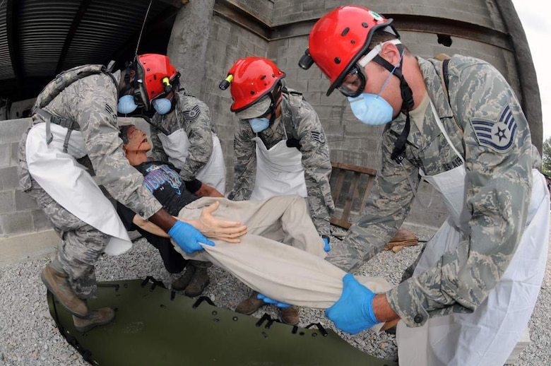 Air National Guard Fatality Search and Recovery Team members collect a simulated casualty from a collapsed parking garage at Muscatatuck Urban Training Complex near Camp Atterbury, Ind., on Aug. 18, 2011, as part of Vibrant Response 12. From left to right are Senior Airman Kevin Woodard and Tech. Sgt. Brittany Ingram of the Kentucky Air Guard; Staff Sgt. Jeffrey Feliciano of the Puerto Rico Air Guard; and Staff Sgt. Jason Gallegos of the Colorado Air Guard. (U.S. Army photo by Staff Sgt. Keith Anderson)
