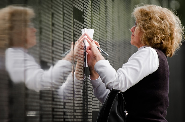 """Jane Lee of Louisville, Ky., creates a rubbing from a soldier's name during closing ceremonies for the Dignity Memorial Vietnam Wall at Resthaven Memorial Park in Louisville, on Sept. 11, 2011. Lee, whose first husband served in Vietnam, chose the name at random because, she said, """"everyone here is important -- each one of these people gave their all in service to our country."""" (U.S. Air Force photo by Maj. Dale Greer)"""