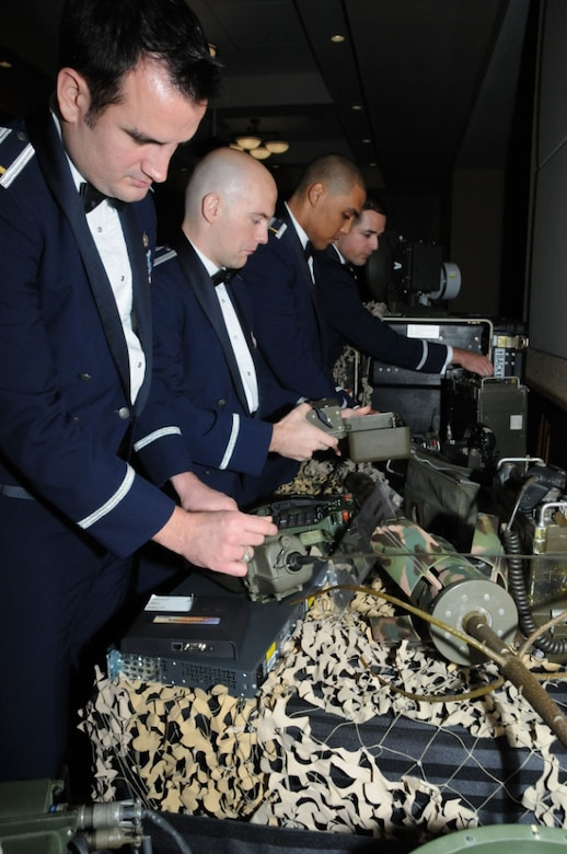 From left, 2nd Lt's Mark Lebedzinski, Brett Cox, Calvin Perez and Nate Kendall examine a display of communication equipment Dec. 7 at a banquet honoring the first graduates of the Air Force's Undergraduate Cyberspace Training course conducted at the 333rd Training Squadron. Lieutenant Perez, stationed with the New York Air National Guard's 213th Engineering Installation Squadron, was part of the first graduating class. (U.S. Air Force photo by Kemberly Groue, 81st Training Wing Public Affairs)