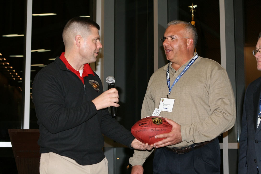 Major Brian Bilski presents a football autographed by wounded, ill and injured Marines to Scott Miller, of Republic Services, at a welcome dinner here at the Irving Convention Center tonight.   The signed football is a token of their appreciation for the support he will provide to the Marines during the time leading up to their attendance at Super Bowl XLV.   The 40 Marines and Marine veterans, supported by the United States Marine Corps Wounded Warrior Regiment, are from military treatment facilities and communities across the nation.