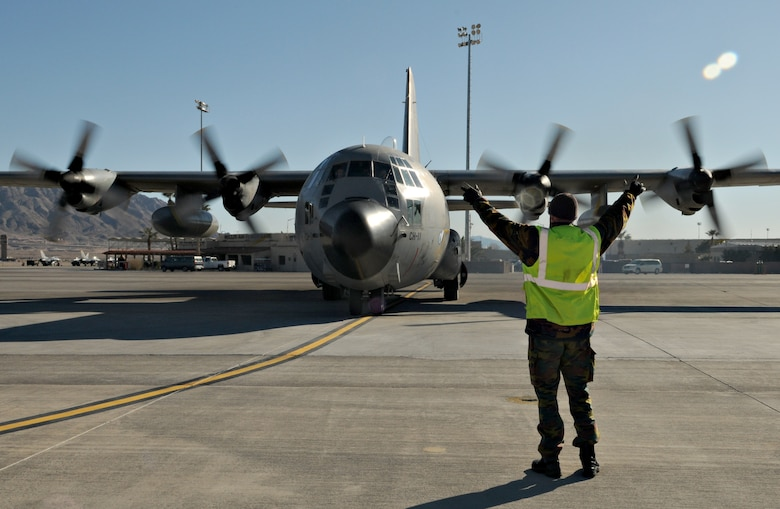 NELLIS AIR FORCE BASE, Nev. -- 1st Cpl. Lesoil Poscol, aircraft maintainer, marshals a C-130 Hercules from the Belgium air force's 20 Squadron Feb. 2 after completing a mission in Red Flag 11-2. The C-130 and Corporal Poscol are deployed from Melsbroek Air Base, Belgium, to participate in the combined exercise that provides a realistic combat training environment to the U.S. and its allies. (U.S. Air Force photo/Staff Sgt. Benjamin Wilson)