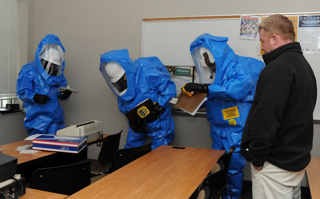 """From left: Staff Sgt. Chris Clark, 241st Engineering Installation Squadron, 118th AW, Senior Airman Tiffany Hogeland, 118th Civil Engineering, and Staff Sgt. Joshua Dow, 118th Bioenvironmental Engineering, assess the room and take readings of the air quality before taking a sample of an """"unknown"""" substance on the table that was simulated to have come from the mail package Jan. 26 during the National Guard Bureau's all hazard response training that took place at the base Jan. 24-28. Far right: a member of L3, which was contracted by NGB, watches the team in action and helps them learn to use the equipment."""