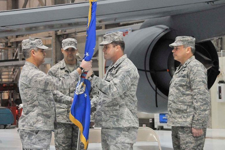 Col. John Puttre, the Director of Staff for Air, accepts the maintenance group guidon from Col. James Locke, the out-going maintenance group commander, on Saturday, February 5, 2011, at Gen. Mitchell International Airport.  Lt. Col. Daniel S. Yenchesky, standing to the right, assumed command of the maintenance group.  (U.S. Air Force photo by Master Sgt. Kenneth Pagel / Released)