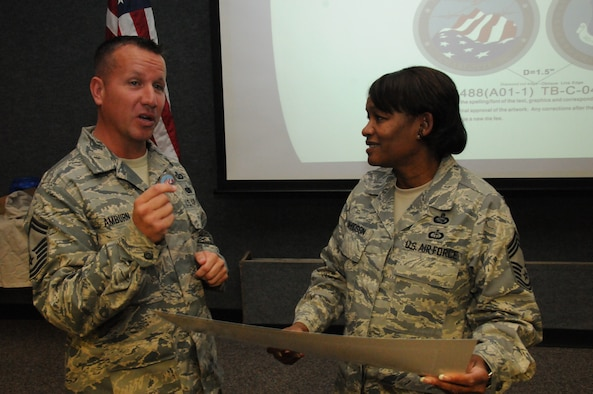 Senior Master Sgt. Chris Amburn presents a newly designed Chapter 7 challenge coin to Chief Master Sgt. Deborah F. Davidson.  Davidson, Paul H. Lankford Enlisted Professional Military Education Center Commandant spoke to the November gathering of the NCO Academy Graduates Association Chapter 7 in Charlotte. Photo by Tech. Sgt. Richard Kerner.