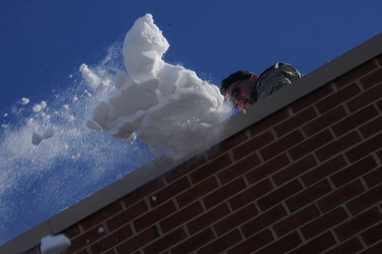 Lt. Col. Kevin McManaman, commander, 118th Airlift Squadron, throws a shovelful of snow from the roof of Tolland High School Jan. 4, 2011, after the town's schools were closed over safety concerns and town officials requested help from the Connecticut National Guard. Approximately 125 Guardsmen were activated and worked from sunrise to sunset there and at the town's middle school. Heavy snow this winter has recently caused several roof collapses across the state. (U.S. Air Force photo by Tech. Sgt. Tedd Andrews)