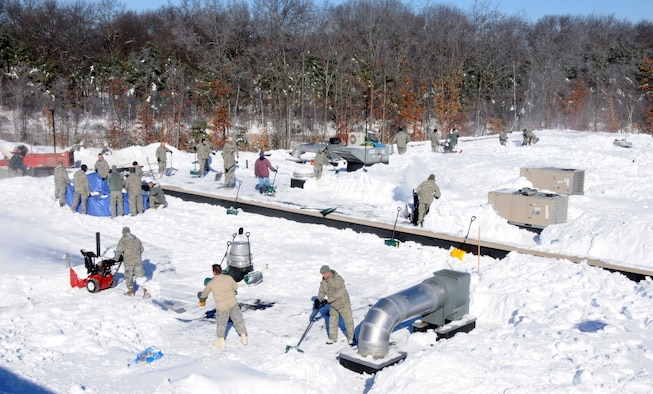 Flying Yankee Airmen with the 103rd Airlift Wing, Conn. Air National Guard, shovel and move snow off the roof of Tolland High School, Tolland, Conn., Jan. 4, 2011 after the town's schools were closed over safety concerns and town officials requested help from the Connecticut National Guard. Approximately 125 Guardsmen were activated and worked from sunrise to sunset there and at the town's middle school. (U.S. Air Force photo by Tech. Sgt. Tedd Andrews)