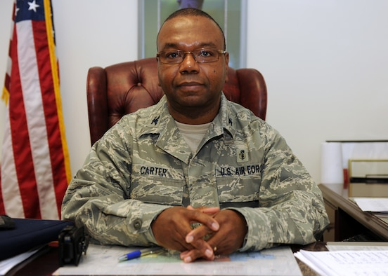 The 174th Fighter Wing Medical Group Commander Col. Wenzell E. Carter, Jr. seated at his desk during the February Unit Training Assembly. (USAF Photo By: Staff Sgt. James N. Faso II/ RELEASED)