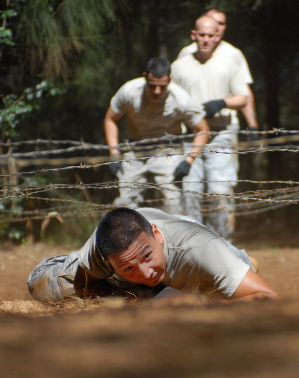 Senior Airman Anthony Elizondo, a 647th Security Forces Squadron Airman from Joint Base Pearl Harbor-Hickam, Hawaii, low crawls under barbed wire as part of an obstacle course Feb. 1, 2011, in Wahiawa, Hawaii. Sixteen security forces members are trying out to attend a two-week Army Air Assault Course beginning May 5, 2011. (U.S. Air Force photo/Staff Sgt. Carolyn Viss)