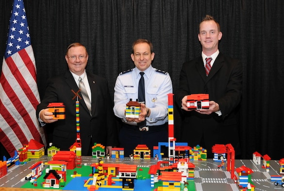 Terry Edwards (left), Maj. Gen. Timothy A. Byers (center) and Troy Peloquin show off some of the miniature houses built out of toy building blocks by attendees at the Professional Housing Management Association Professional Development Seminar in New Orleans. The building blocks, which were available at the Air Force's Housing trade-show booth to promote teamwork and customer service as building blocks for communities, were donated to the local school district to be enjoyed by local students. Mr. Edwards is the director of the Air Force Center for Engineering and Environment. General Byers is the Air Force civil engineer. Mr. Peloquin is the donations coordinator for the Louisiana Recovery School District.