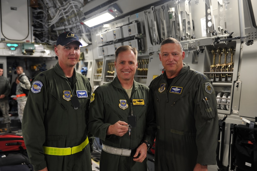 Lt. Col. Todd Grooms, 17th Airlift Squadron director of operations, Col. John Wood, 437th Airlift Wing commander and Gen. Gary North, commander of Pacific Air Forces, Air Component Commander for U.S. Pacific Command and Executive Director, Pacific Air Combat Operations Staff at Joint Base Pearl Harbor-Hickam, Hawaii, pose for the camera after presentation of the ceremonial keys to Joint Base Charleston's newest aircraft. (U.S. Air Force Photo illustration by Tech. Sgt. Chrissy Best)