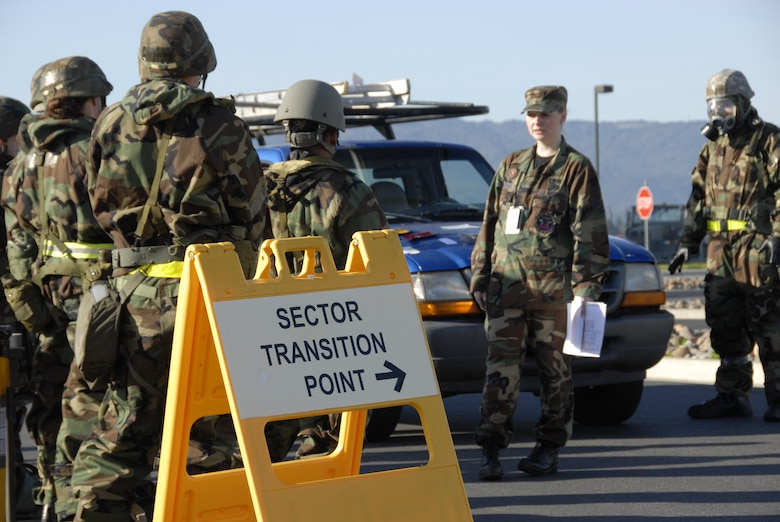 Staff Sgt. Alana Groshong, an emergency management technician from the 129th Civil Engineering Flight, briefs proper sector transition precedures to members dressed in Mission Oriented Protective Posture suits during war skills training at Moffett Federal Airfield, Calif., Feb. 5, 2011. The 129th Rescue Wing is preparing for an upcoming Operation Readiness Inspection in December 2011. (Air National Guard photo by Tech. Sgt. Ray Aquino/RELEASED)